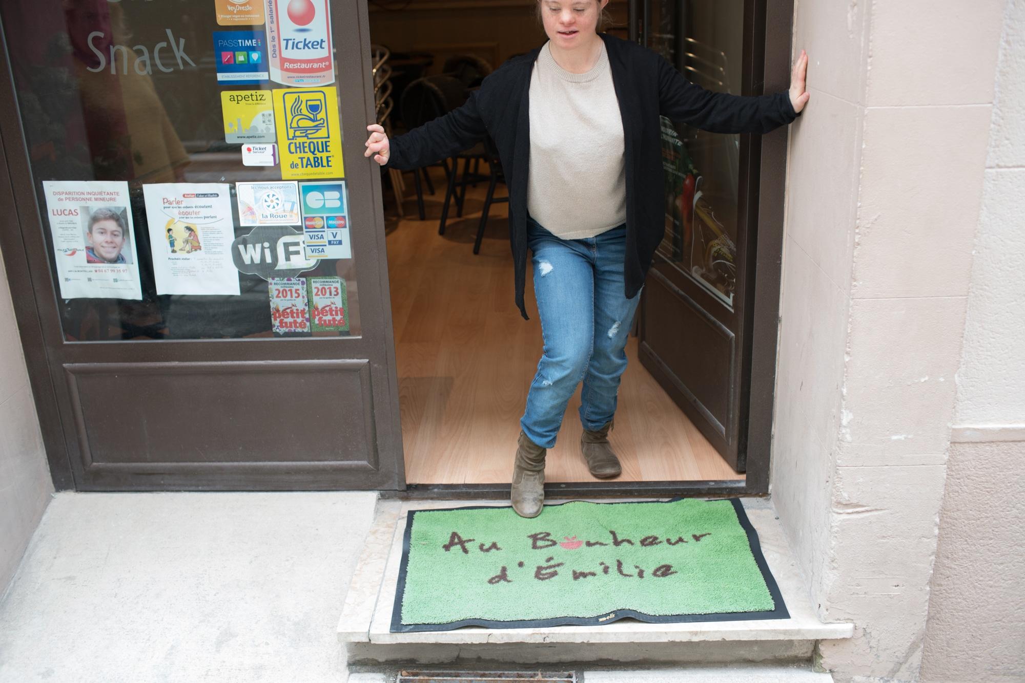 Emilie Tient Son Téléphone Émilie Se Tient Dans Lu0027encadrure De La Porte Du  Restaurant.