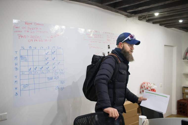 Mornay Esterhuyse se tient devant un tableau sur lequel figure un planning. Il a un pli à la main et un sac à dos sur les épaules.