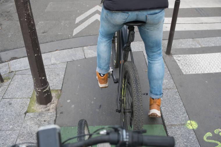 Mornay vu de dos et en plongée, sur son vélo : on peut apercevoir une pièce ajoutée à la pédale gauche.