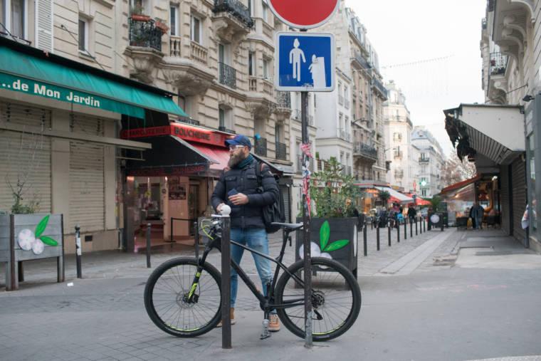 Mornay se tient près de son vélo, qui est posé contre un panneau d'indication.
