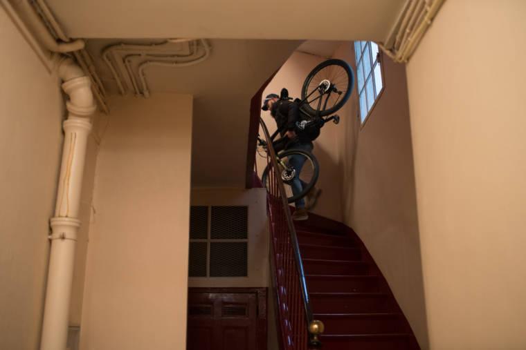 Mornay transporte son vélo sur son dos dans une cage d'escalier.
