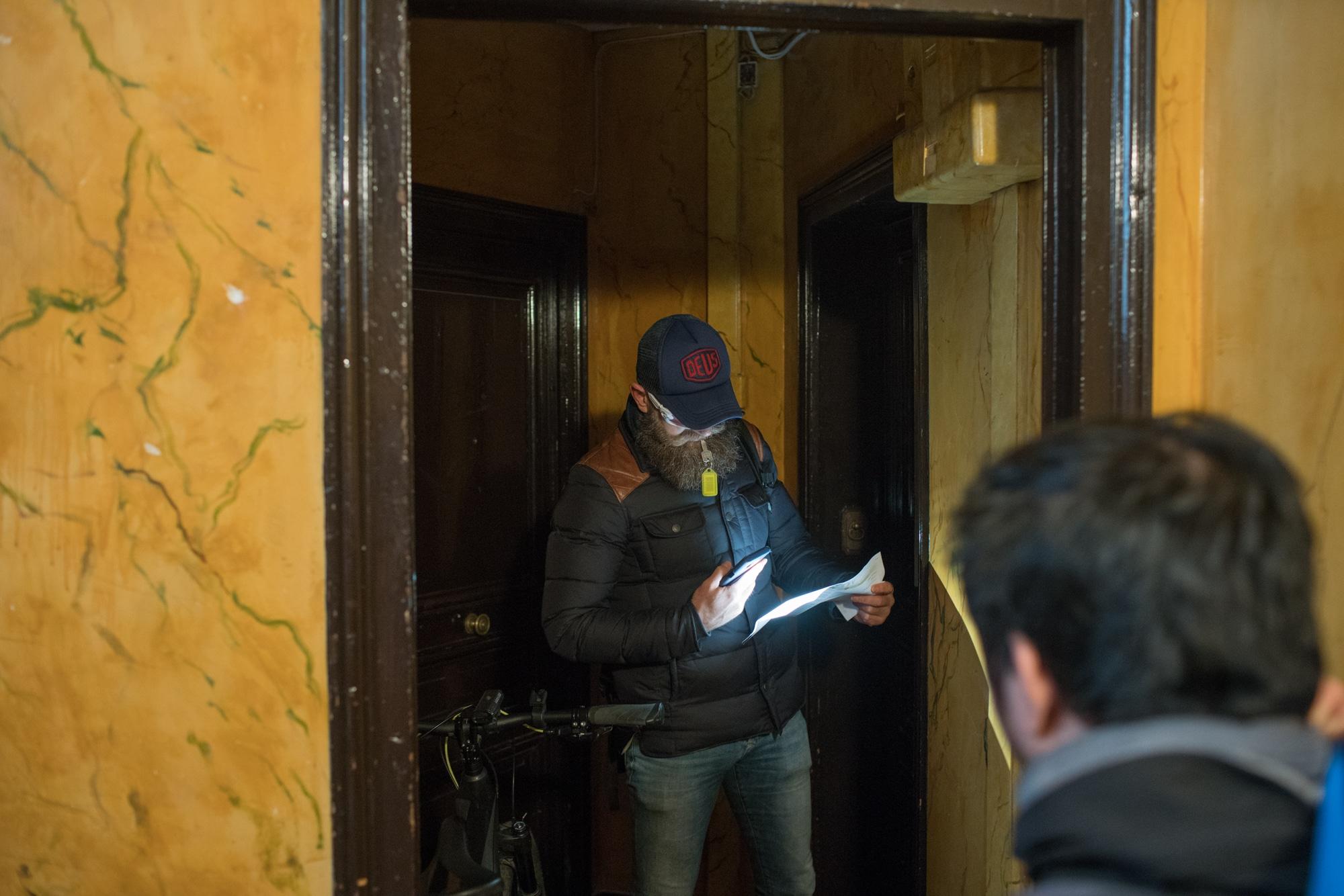 Devant une porte d'appartement, Mornay examine un papier à la lumière de son téléphone.