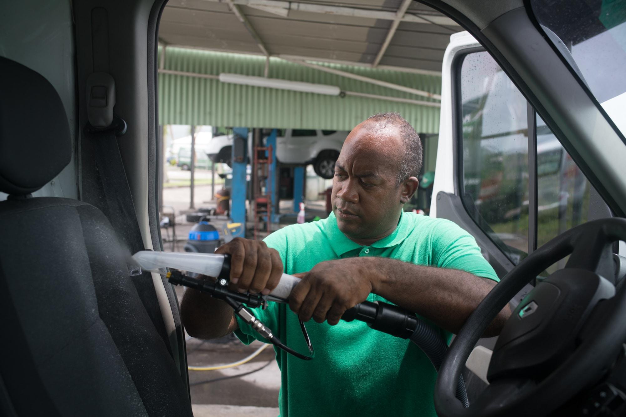 Du côté conducteur, Fred applique un produit moussant sur le siège du véhicule.