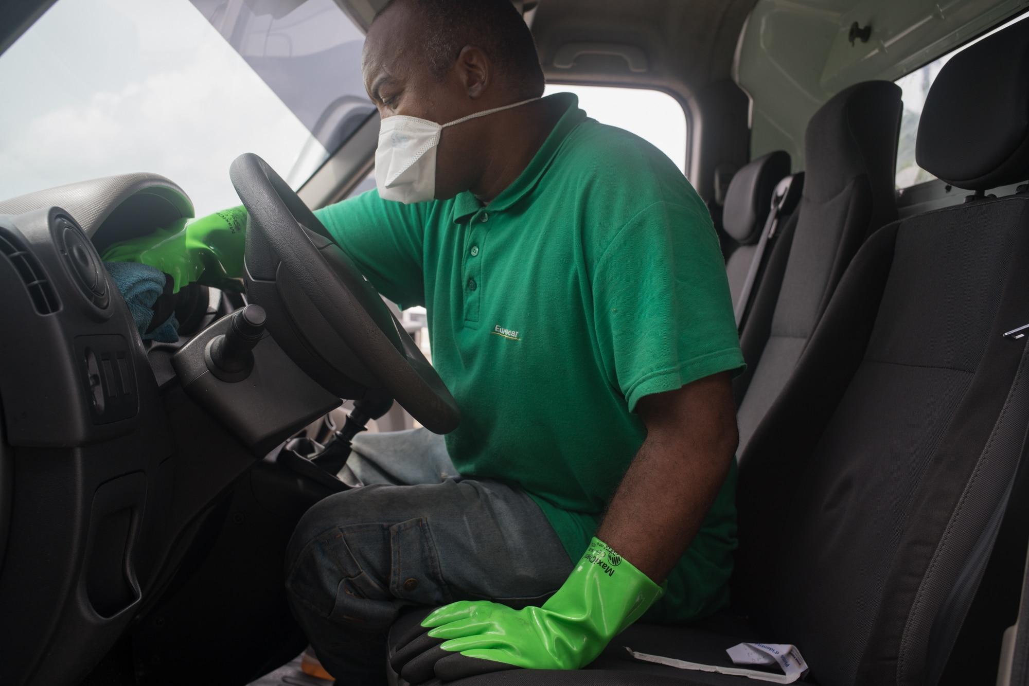 Équipé de gants en caoutchouc et d'un masque, Fred applique un produit nettoyant sur le tableau de bord.