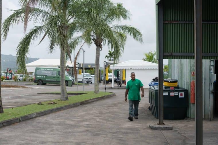 Fred longe un container en marchant. Derrière lui on aperçoit des lave-autos.