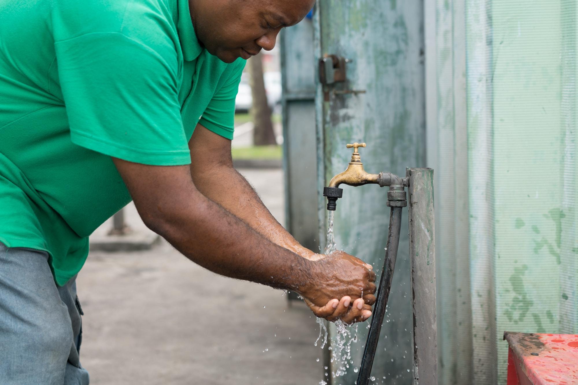 Fred, penché vers l'avant, se laver les mains auprès d'un robinet extérieur.