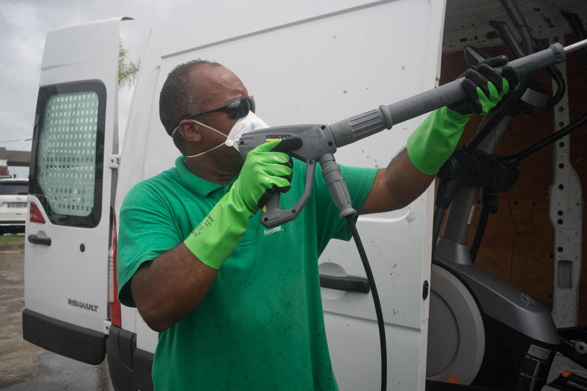 Fred porte un masque sur le nez et la bouche et passe le Kärcher à l'intérieur du véhicule.