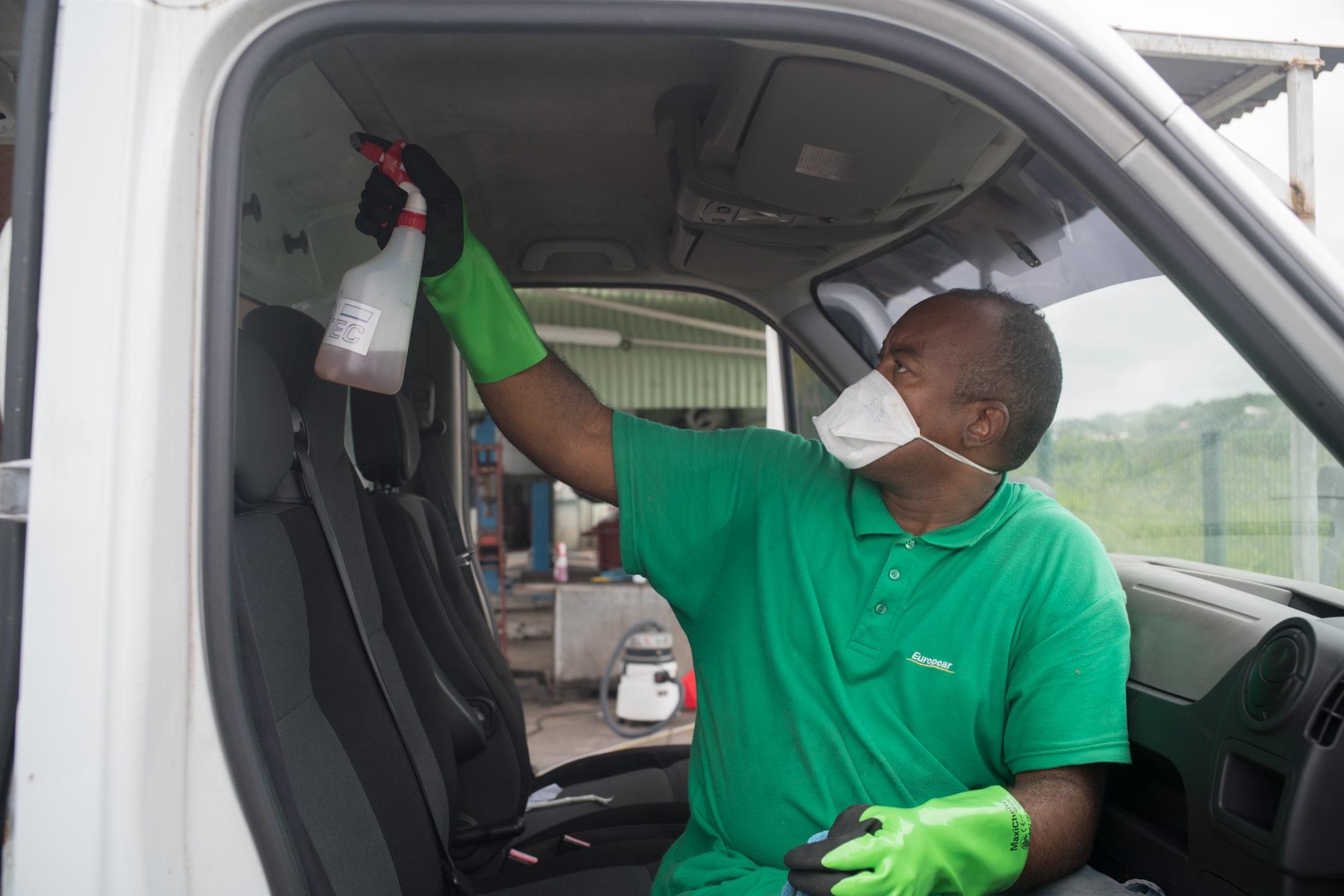 Installé à l'intérieur du véhicule, Fred vaporise un produit sur le plafond du côté passager.