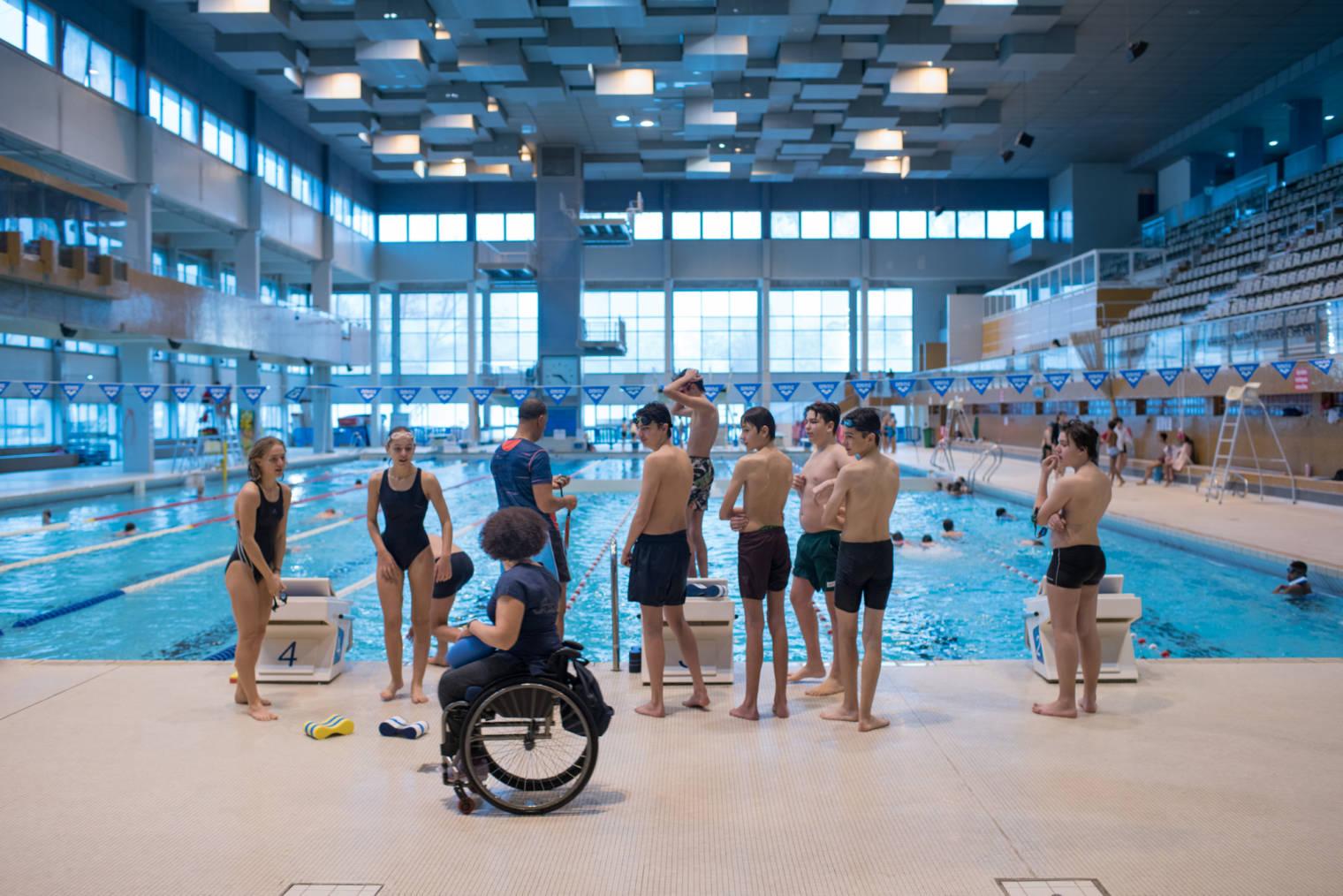Hadda s'adresse à de jeunes nageurs dans une piscine municipale.