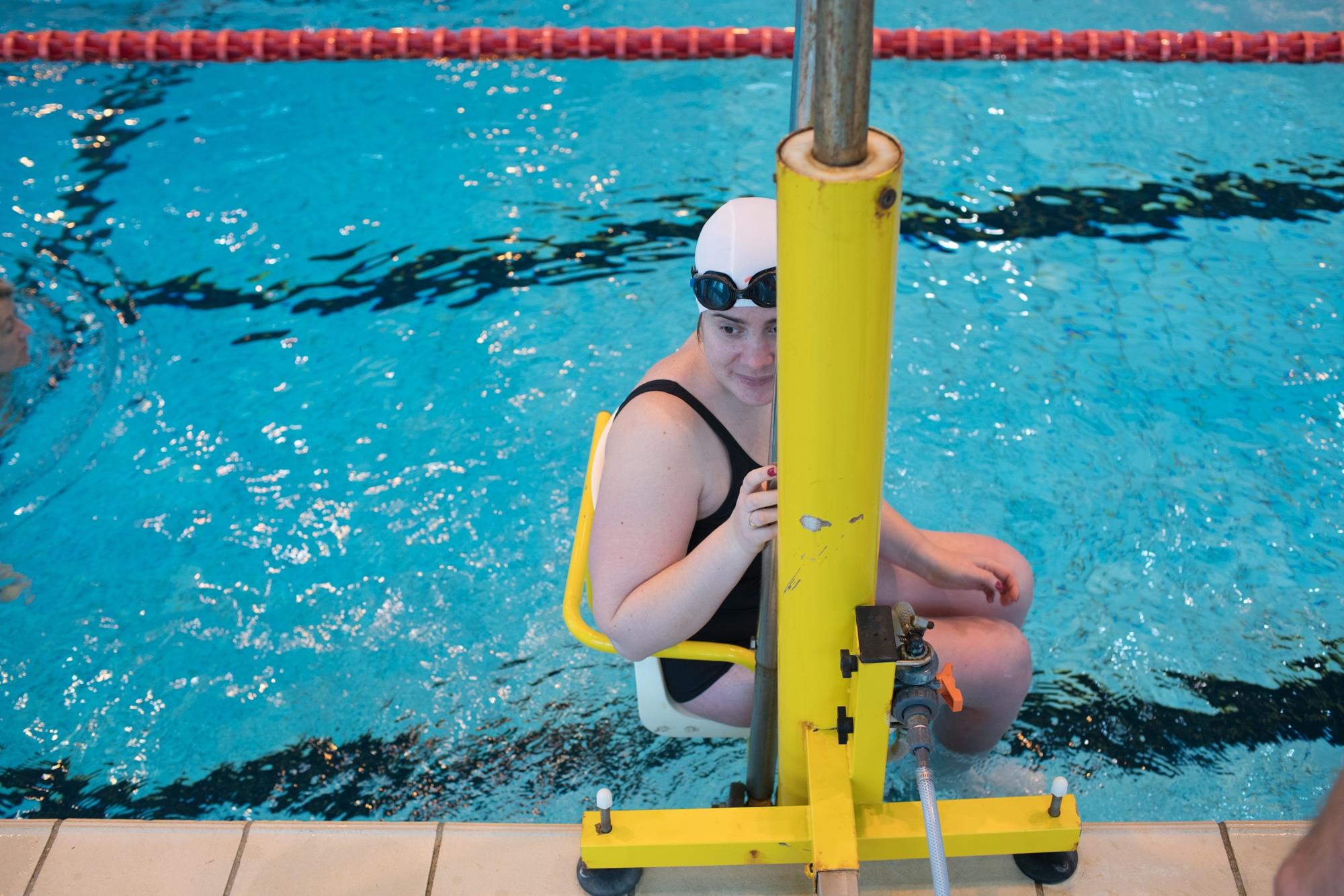 L'élève descend dans le bassin à l'aide d'un mécanisme automatisé.