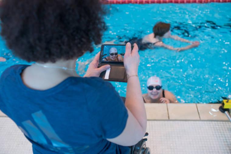 Hadda, de dos, prend une photo de son élève dans l'eau, souriante.