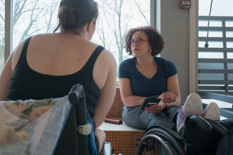 Hadda, assise dos à la vitre, les pieds appuyés sur son fauteuil roulant, discute avec une élève en fauteuil.