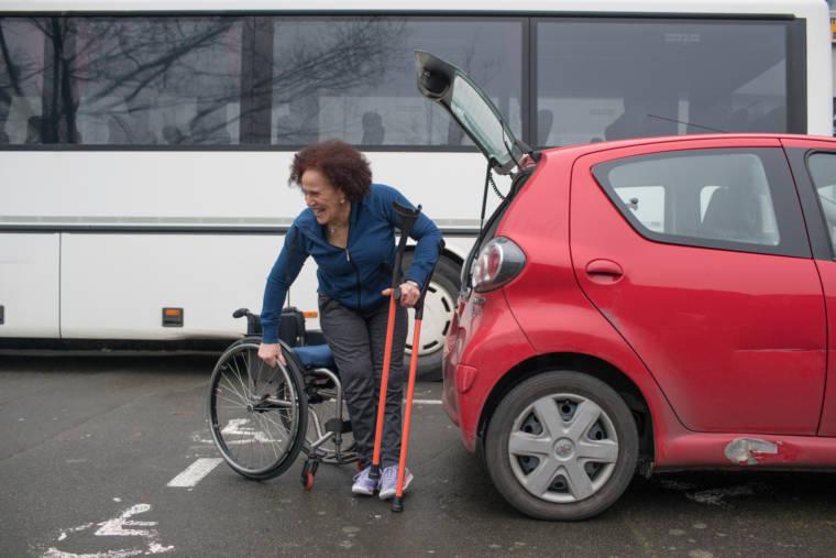 Devant le coffre de sa voiture rouge, Hadda, souriante, s'appuie sur ses béquilles pour se hisser dans son fauteuil.