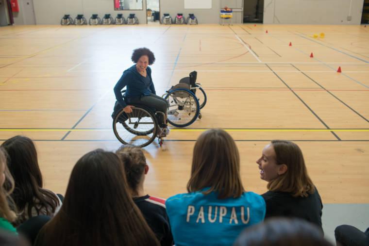 Hadda sillonne un terrain de basket avec un grand sourire en faisant face à de jeunes élèves pour les sensibiliser au handicap.