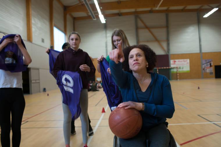 De face, un ballon de basket à la main, Hadda désigne un objet que l'on ne voit pas à ses élèves.