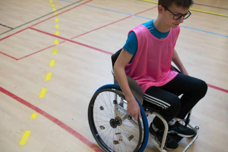 Un élève équipé d'un dossard rose sillonne le terrain de basket en fauteuil roulant.