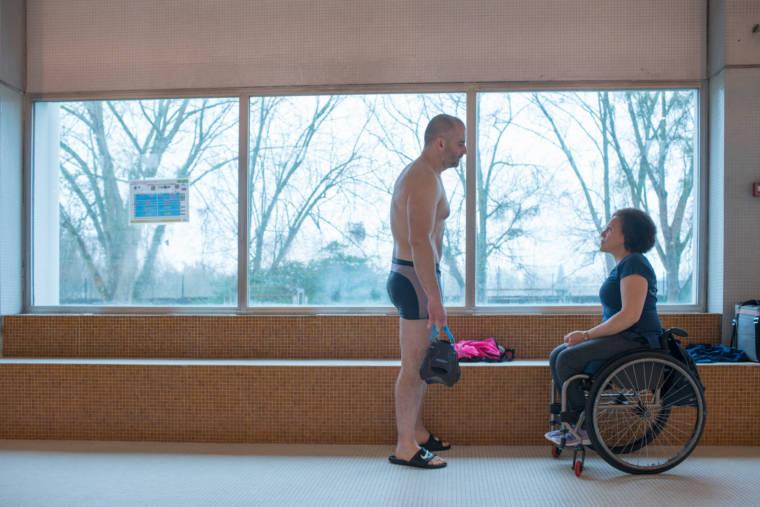 Hadda fait face à un nageur adulte devant une grande vitre donnant sur l'extérieur de la piscine.