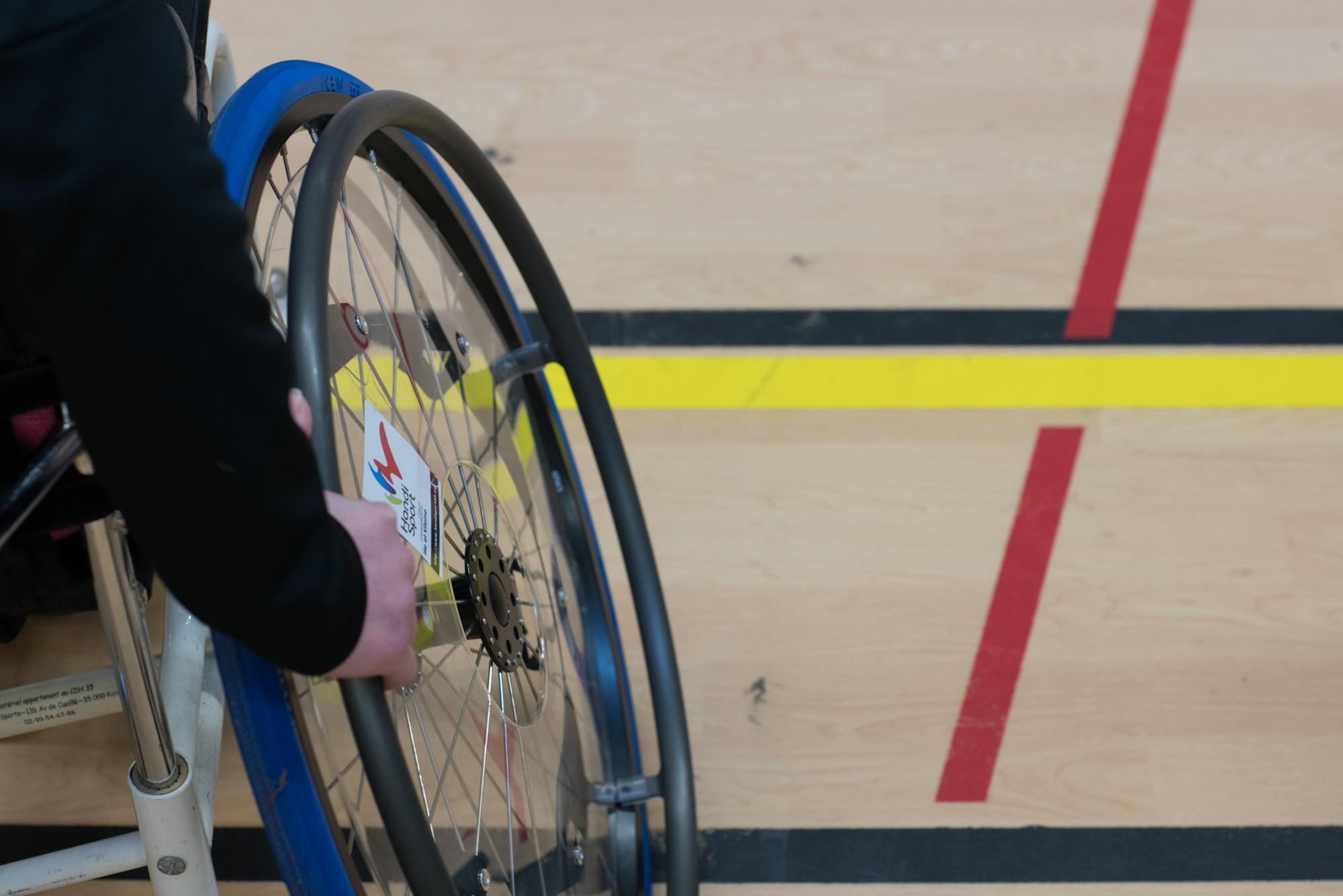 Gros plan sur une des roues d'un fauteuil roulant de sport. On peut lire l'inscription Handisport.