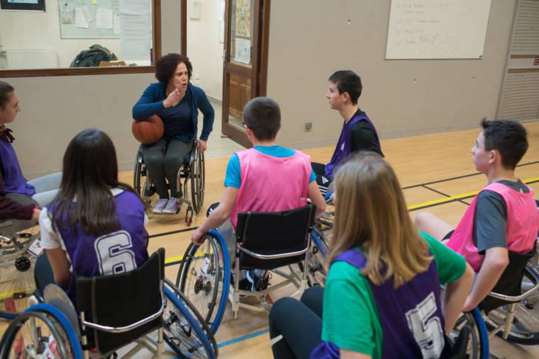 Hadda, un ballon de basket sous le coude, s'adresse à ses élèves avec passion. Tous la regardent attentivement.