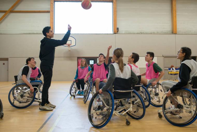 Un élève, debout, lance un ballon pour engager un entre-deux à des élèves en fauteuil.