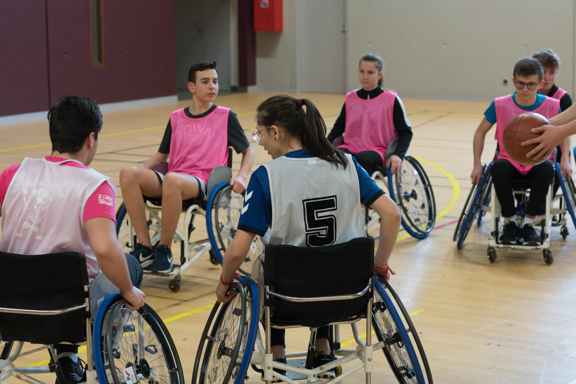 Deux équipes d'élèves s'affrontent en fauteuil sur le terrain de basket.