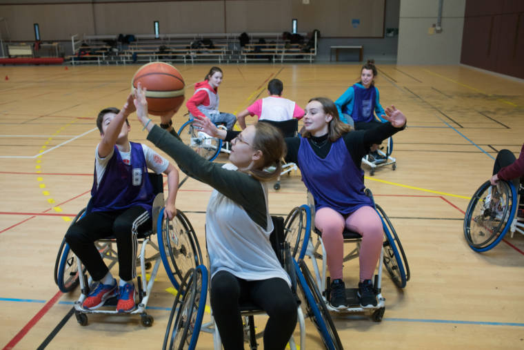 Deux équipes s'affrontent au basket en fauteuil roulant.