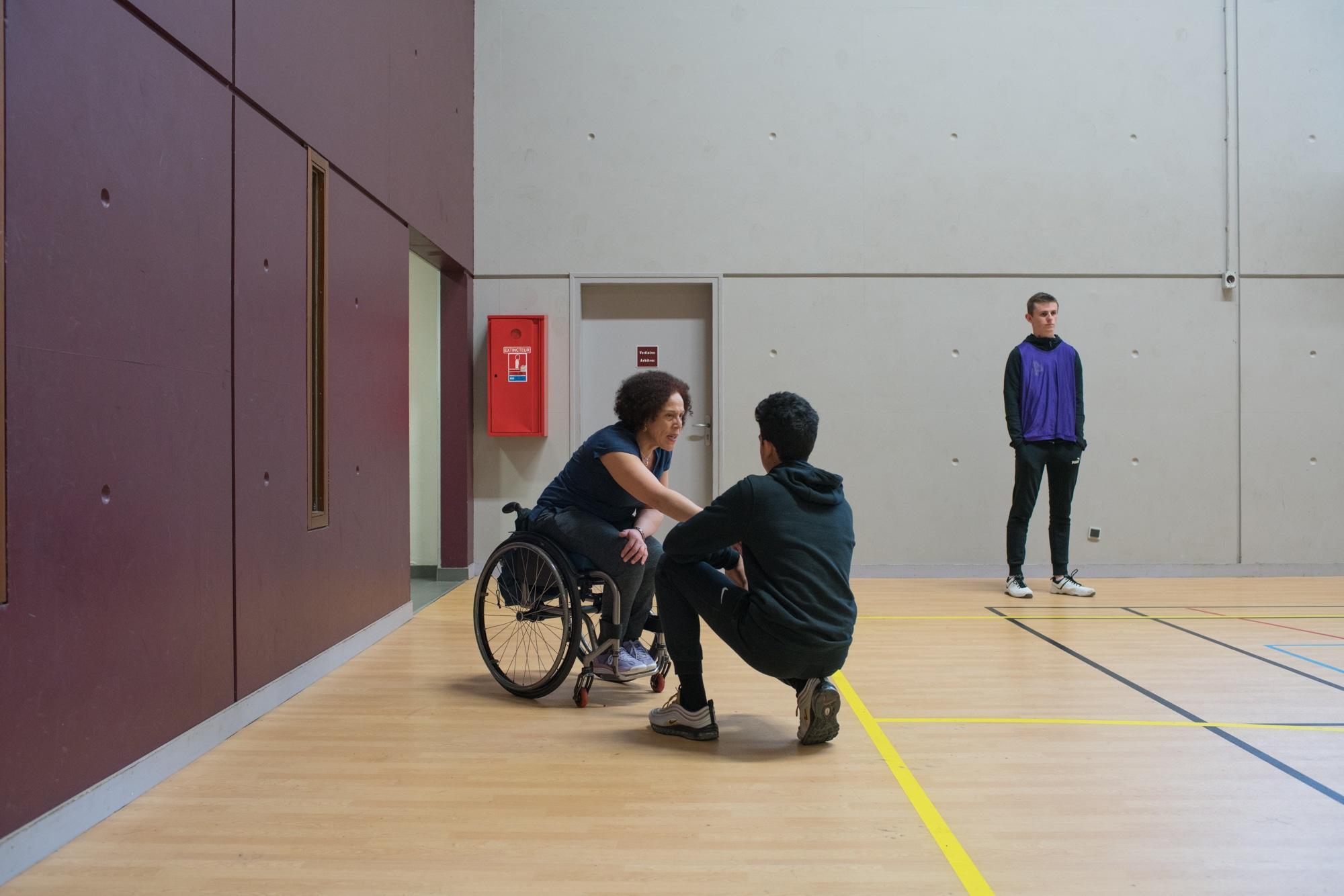 Un élève est accroupi devant Hadda, qui lui saisit la main en s'adressant à lui.