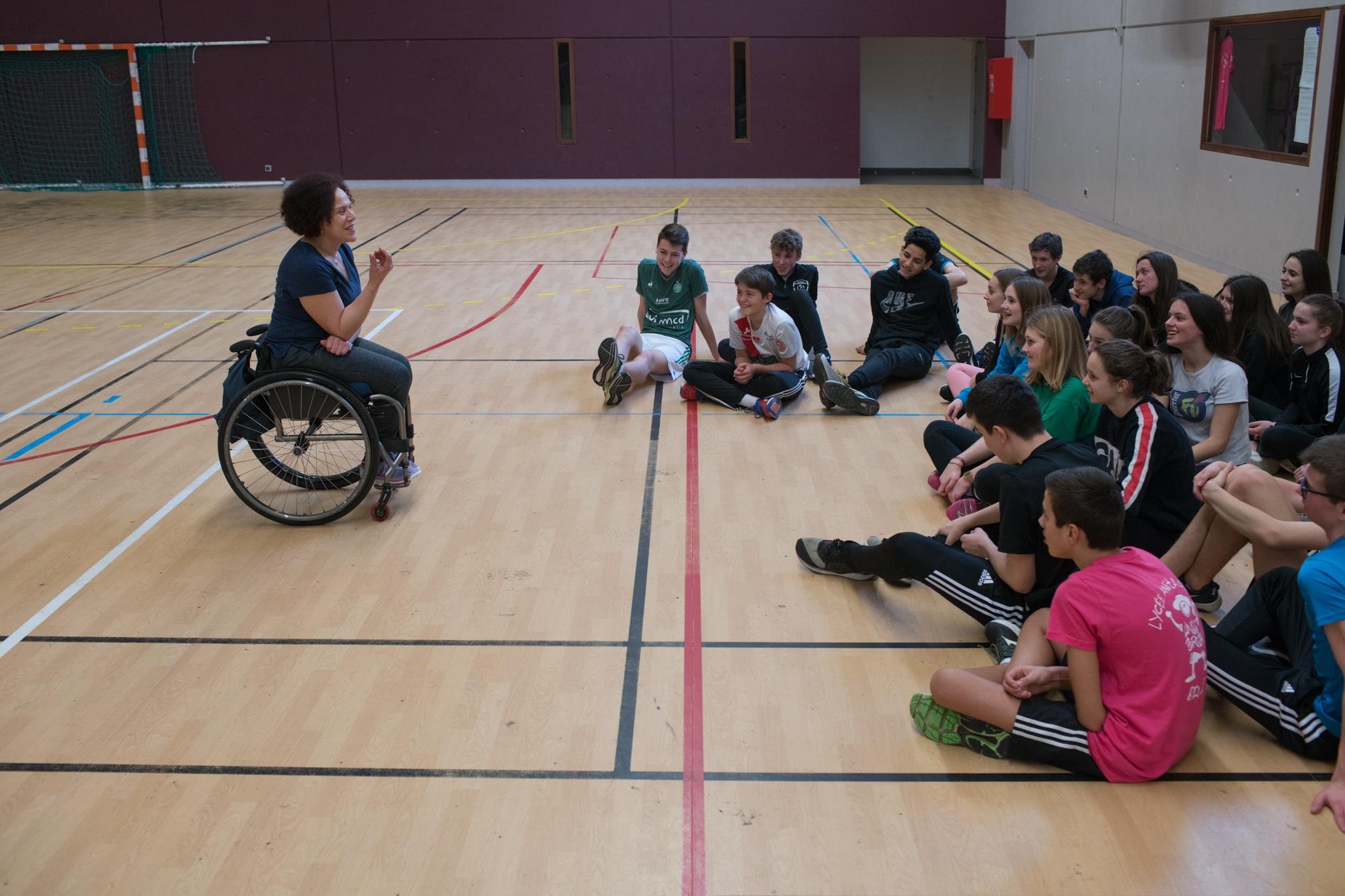 Hadda s'adresse à un parterre d'élèves assis. Ils n'ont plus leur fauteuil roulant et l'écoutent attentivement.