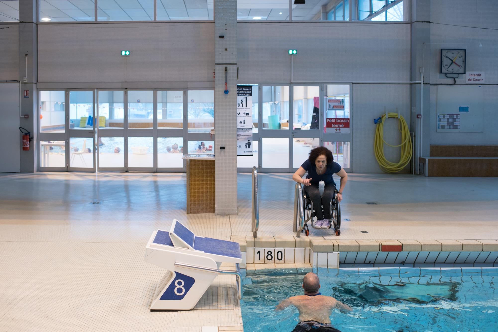 Hadda, penchée en avant sur son siège, vers le niveau de l'eau, s'adresse à un nageur.