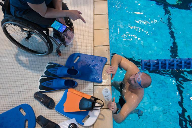 Hadda pointe du doigt un nageur en s'adressant à lui. Elle tient son téléphone dans l'autre main. Le nageur, accoudé au bord de la piscine, a devant lui des accessoires divers.