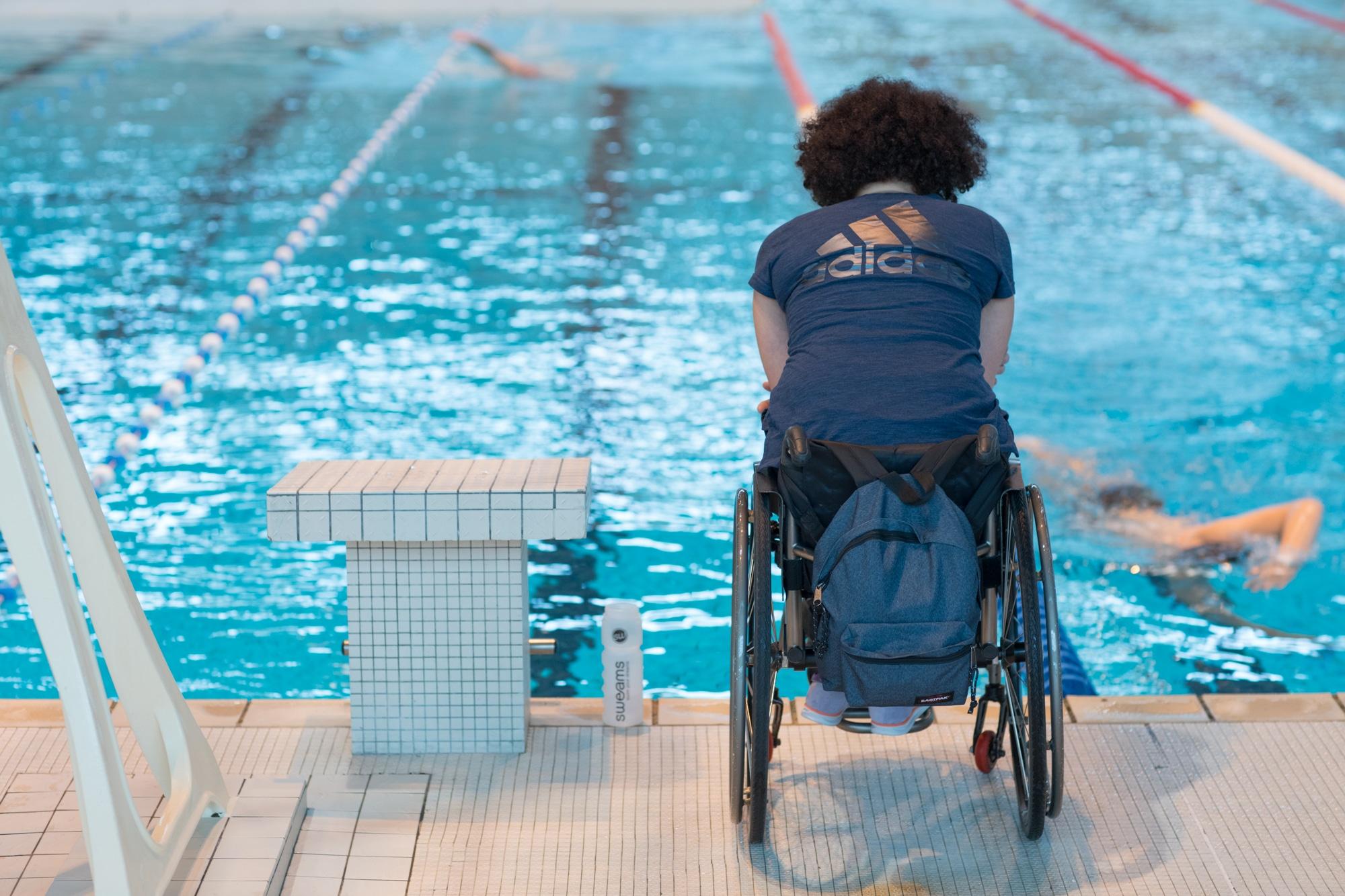 Hadda, de dos, bras croisés, observe son élève en train de nager.