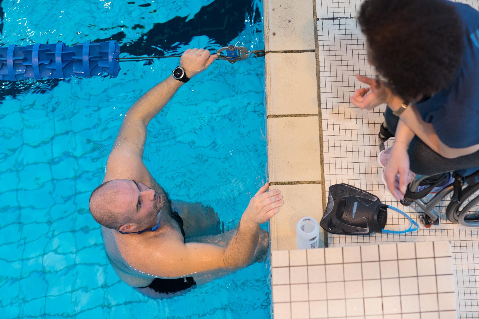 Hadda s'adresse à son élève, accroché au rebord de la piscine.