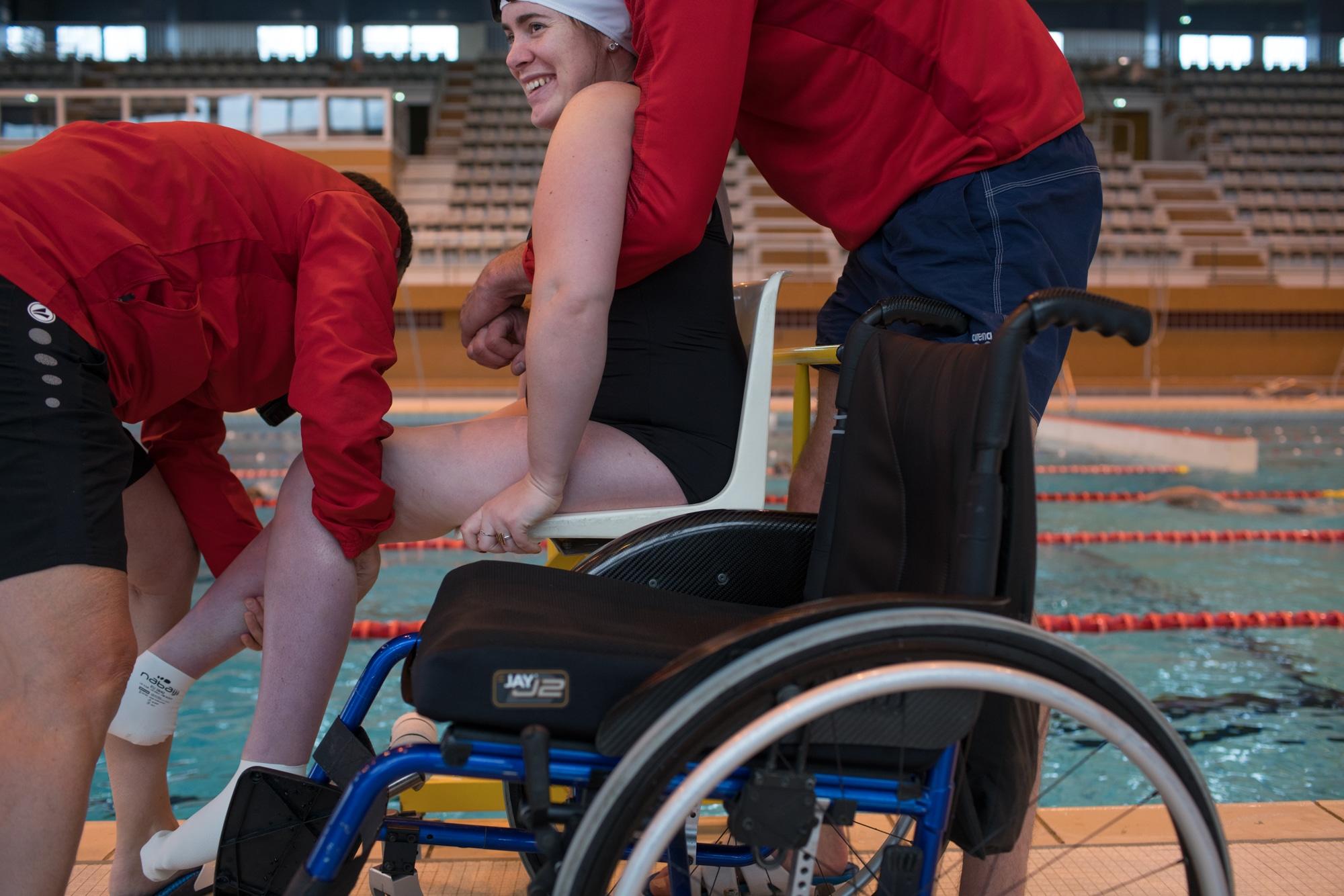 Une élève d'Haddam, équipée d'un maillot et d'un bonnet, est aidée par deux personnes pour s'extirper de son fauteuil roulant.
