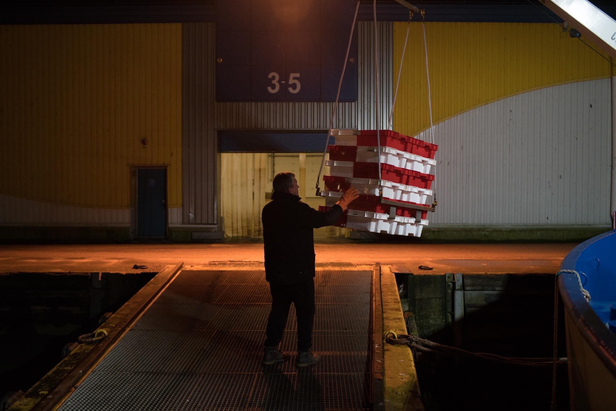 Sur le quai, une personne réceptionne les caisses portées par la grue.