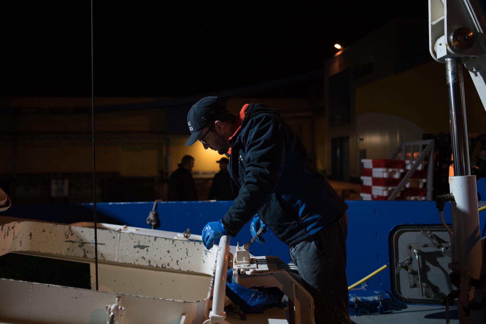 José Leprêtre, sur le pont, manipule la grue à l'aide d'une commande électrique.