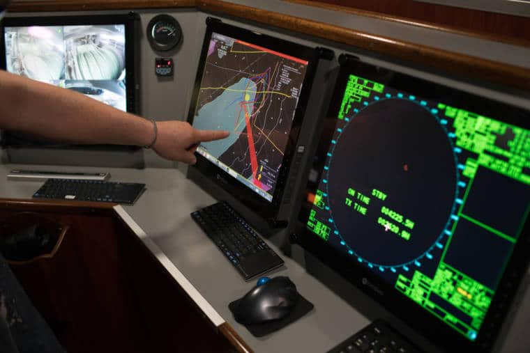 La main de José désigne deux écrans affichant des données de navigation