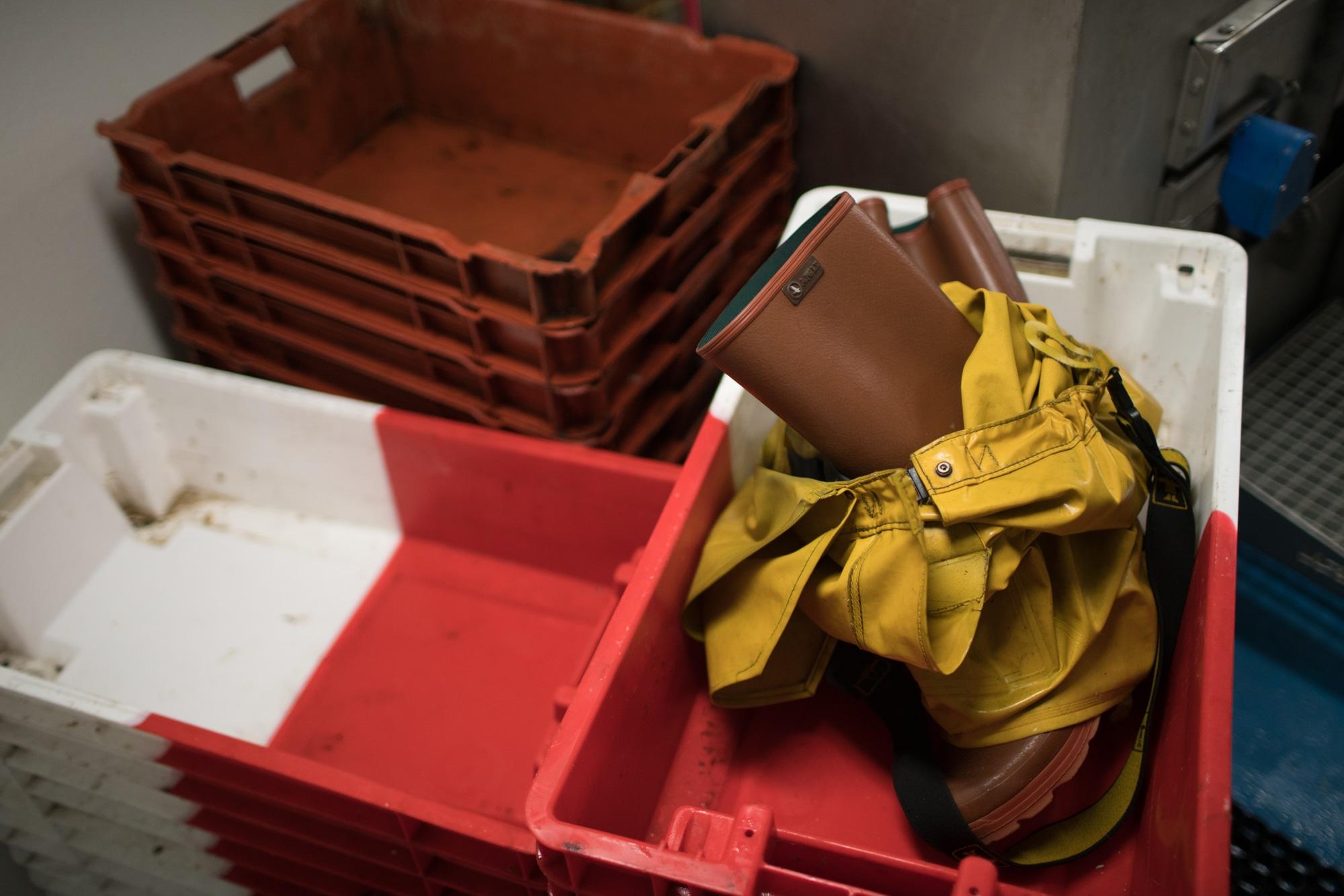 Une paire de bottes et une salopette en ciré jaune sont posées sur des piles de caisses.