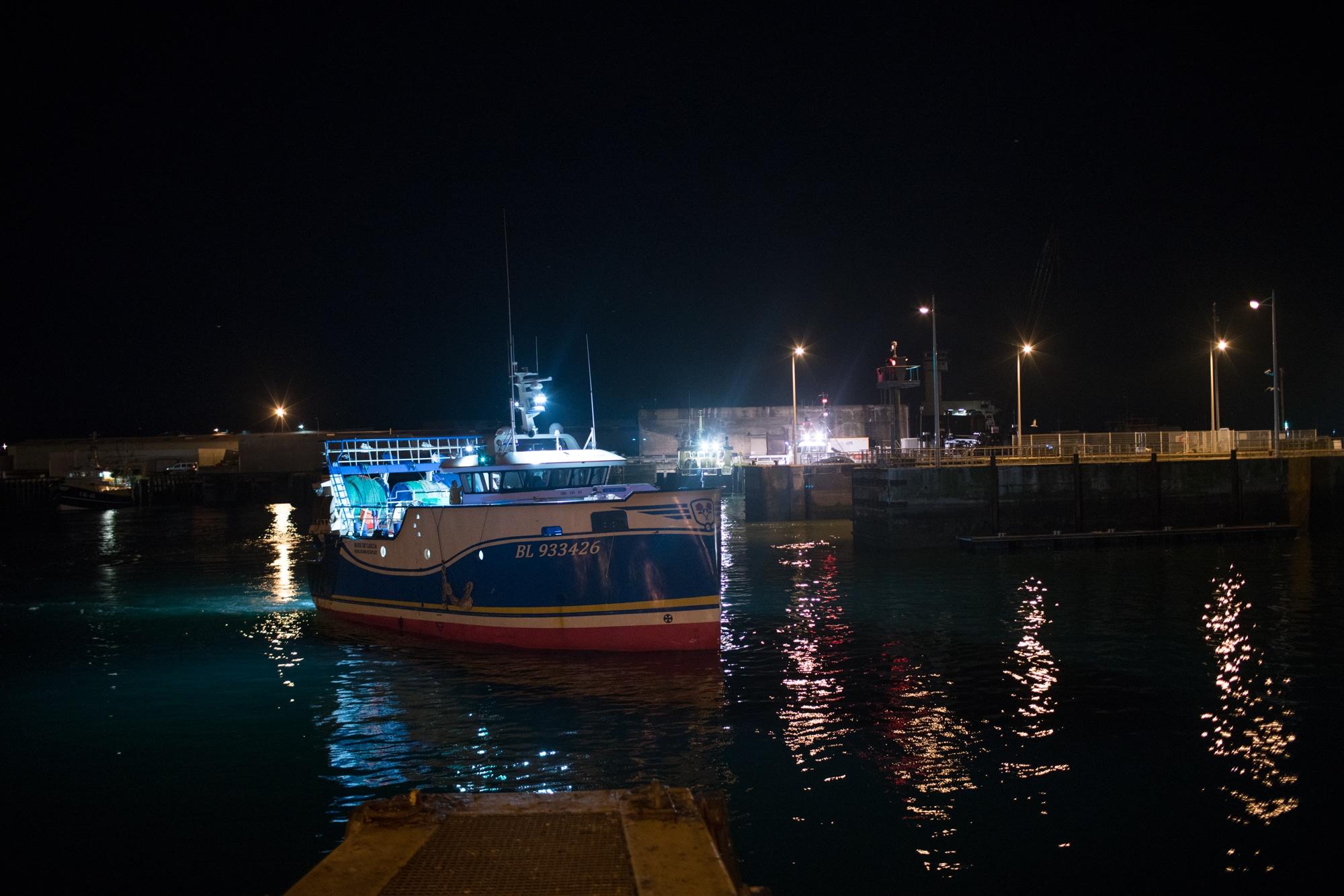 Un bateau navigue dans les eaux du port, la nuit