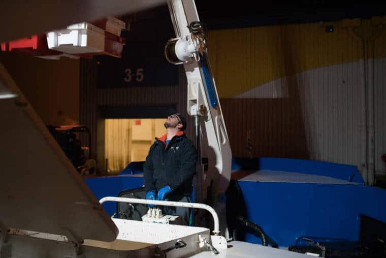 José Leprêtre manipule une grue pour extraires les caisses de poisson