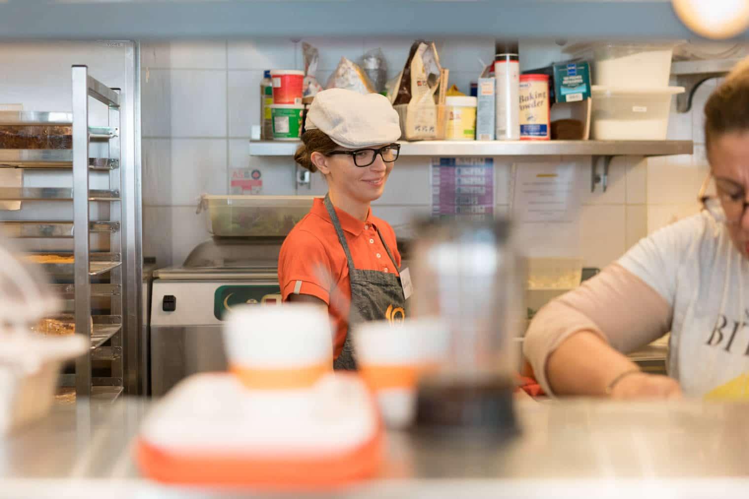 Laetitia, en cuisine, sourit à une collaboratrice en la regardant travailler.