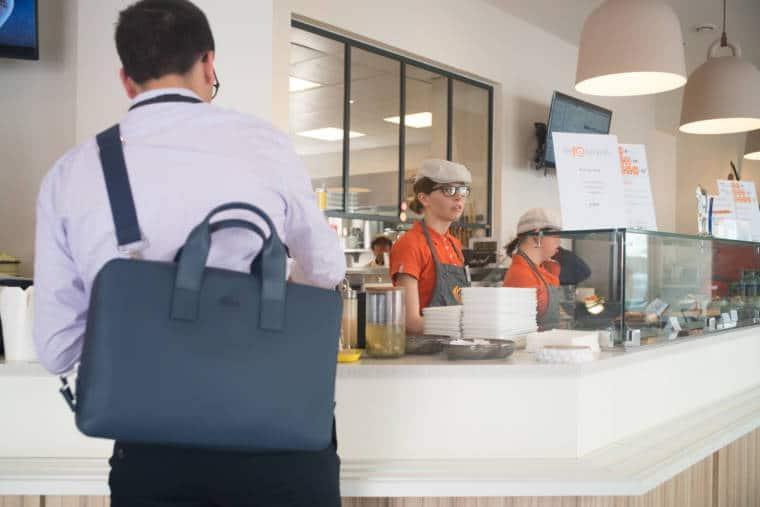 Laetitia se tient derrière un comptoir, en salle, sur lequel on aperçoit de la nourriture et des assiettes. Au premier plan, un homme portant un sac est accoudé au comptoir.