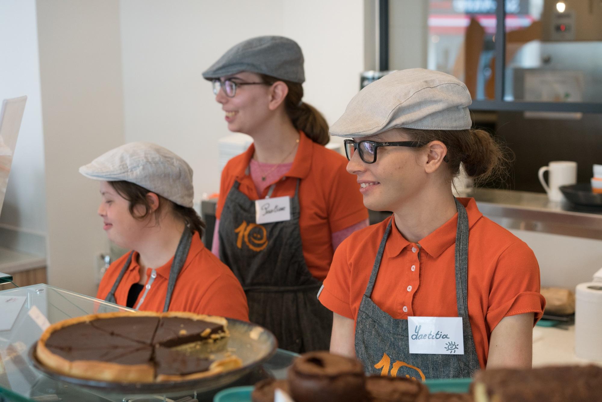 Laetitia se tient aux côtés d'Inès et d'une autre collaboratrice derrière le comptoir. Sur celui-ci on aperçoit des tartes au chocolat.