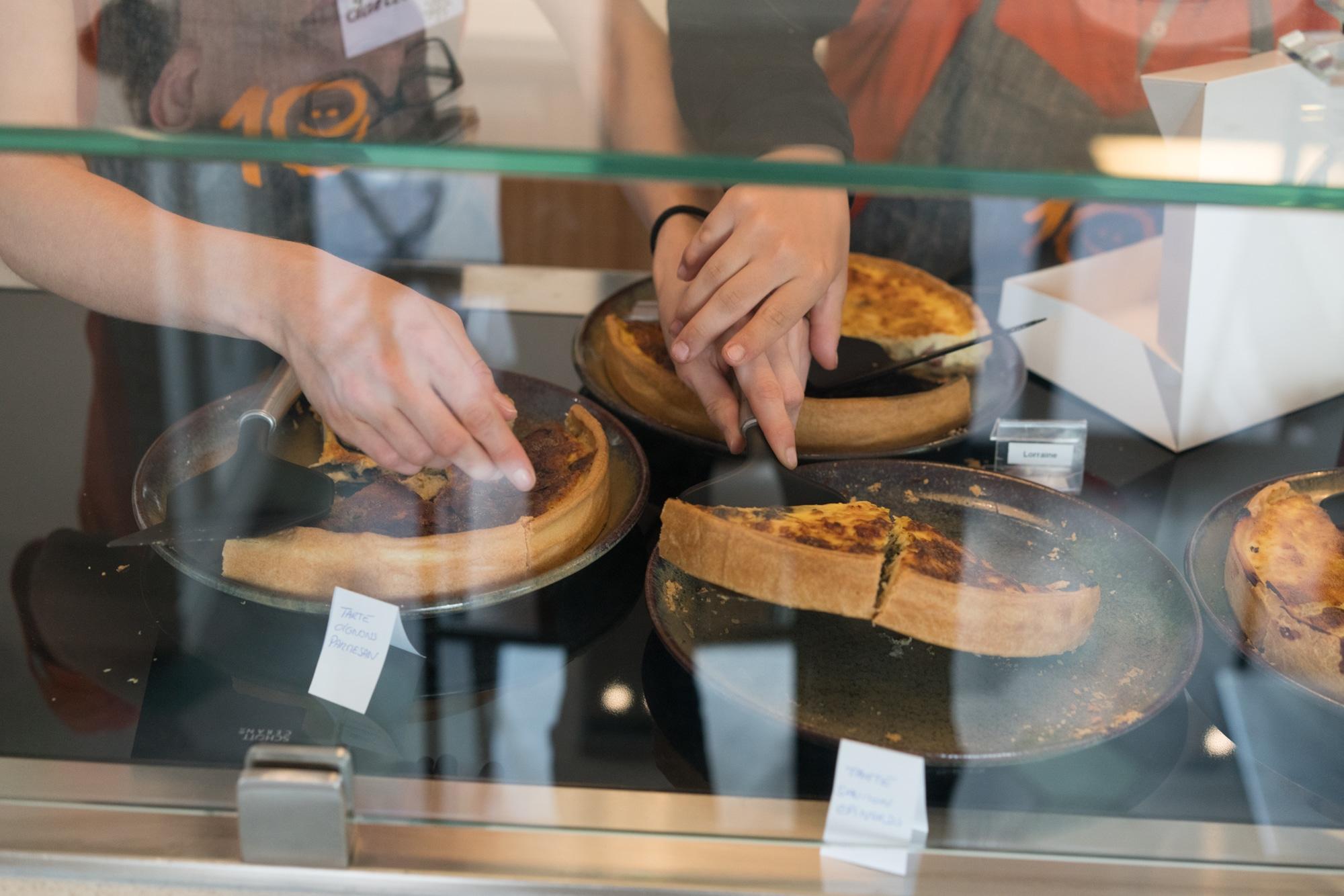 À travers la vitrine du comptoir, on aperçoit une main guider une autre main en train de manier une pelle à tarte pour servir une part.