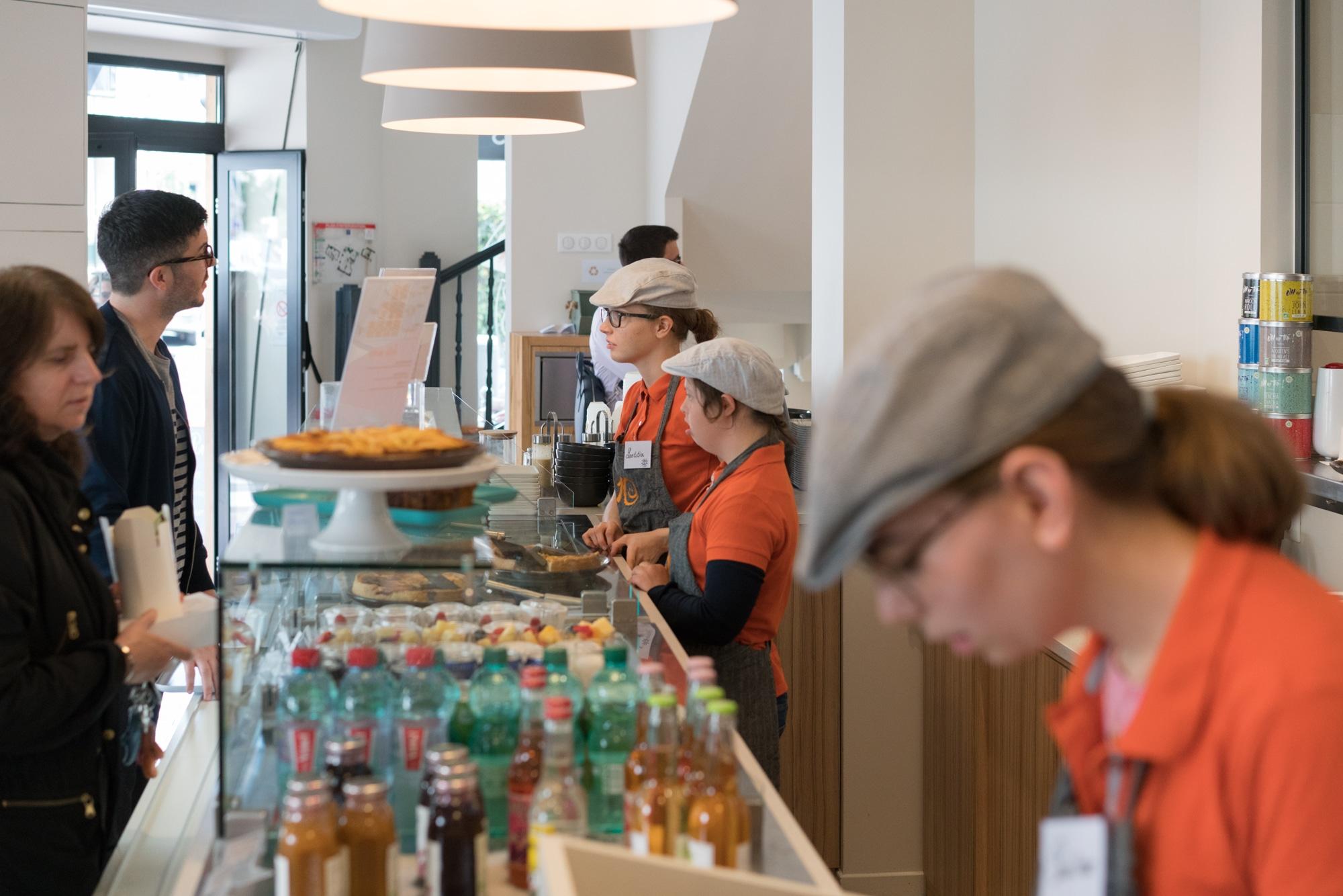 D'un côté du comptoir, Laetitia est entourée de ses collaborateurs, chacun affairé, tandis que de l'autre les clients commandent et regardent la vitrine.