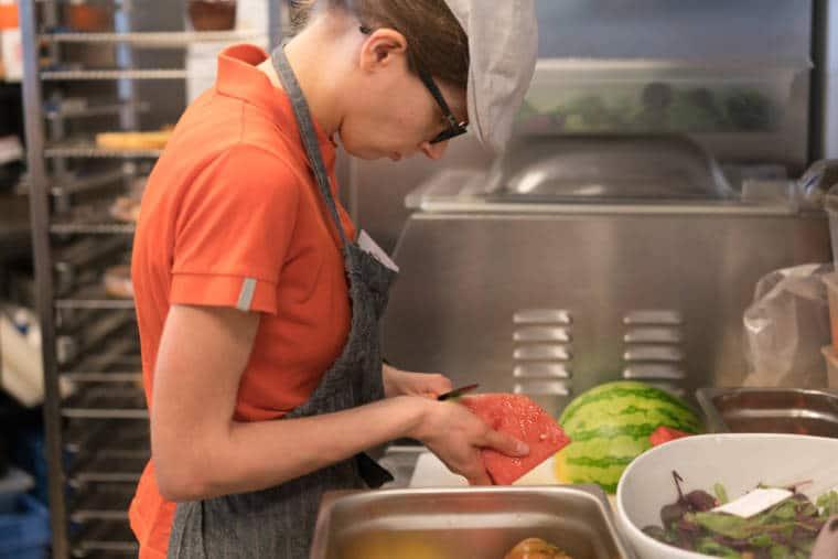 Laetitia prépare une pastèque en cuisine.