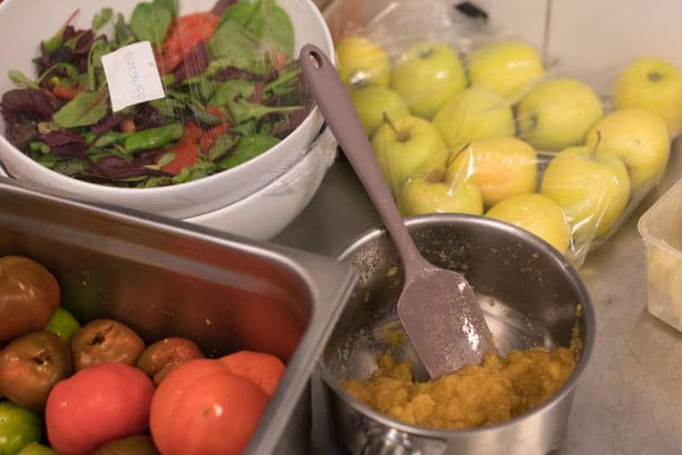 Des tomates, des pommes et une salade ainsi qu'une compote de pommes sont disposés sur un plan de travail.