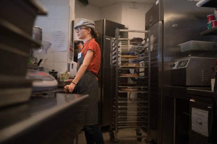 Laetitia est appuyée sur un plan de travail. Derrière elle on aperçoit une étagère mobile sur laquelle sont disposés des tartes.