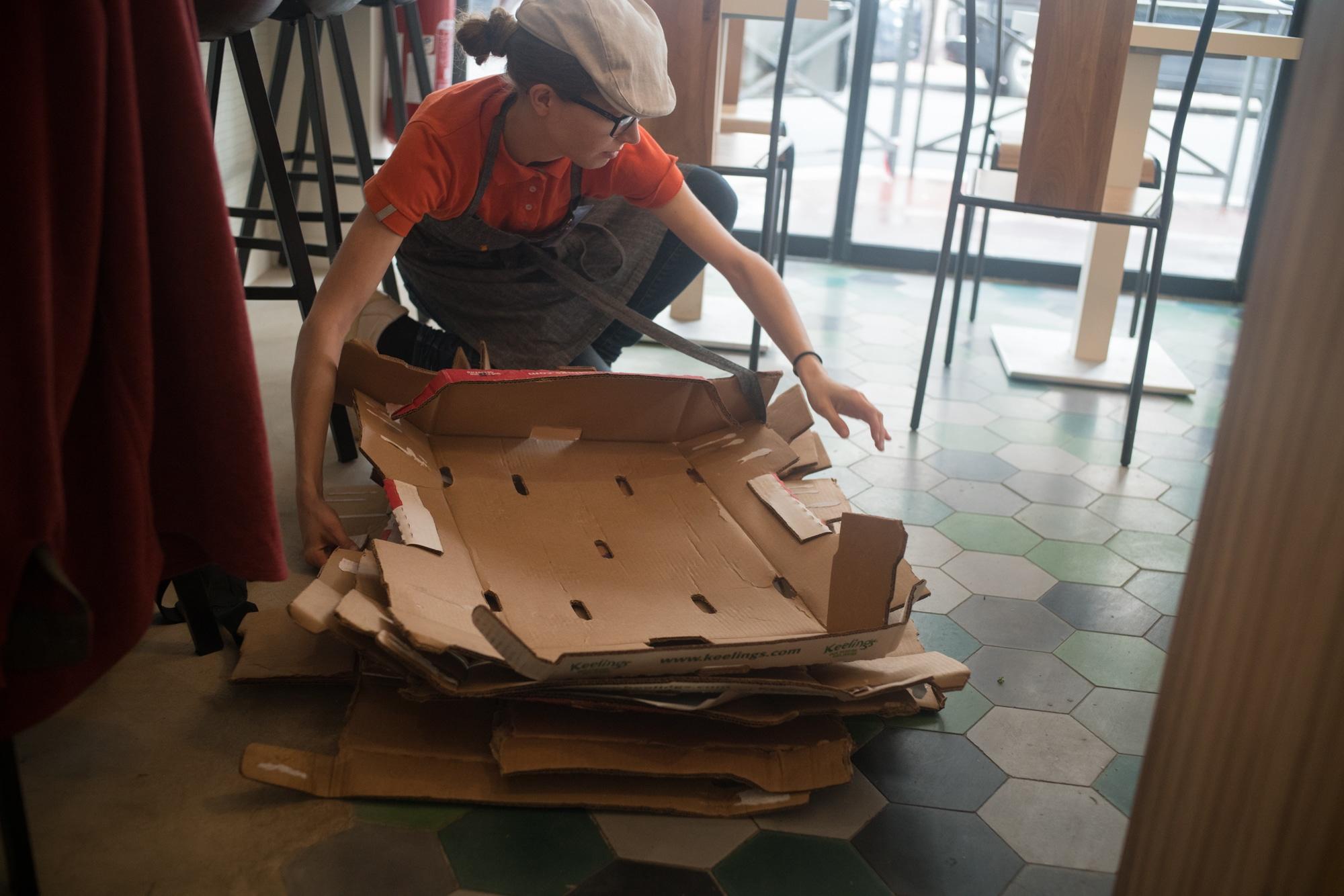 En salle, accroupie, Laetitia rassemble des cartons d'emballage vides.