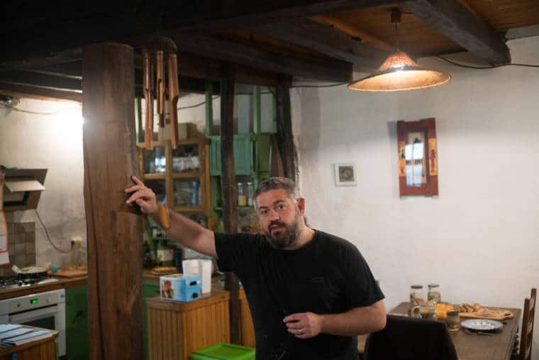 Laurent Ferraglio est adossé à une poutre en bois dans sa maison
