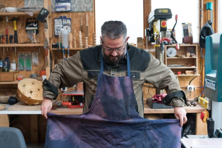 Laurent enfile un tablier mauve dans son atelier